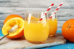 Glass of orange juice with straws, spoon and slices on cutting board on color wooden background